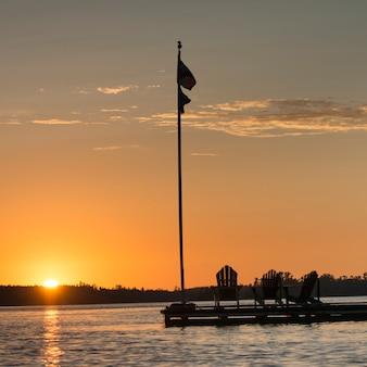 Adirondack Stühle und Flagge auf einem Dock bei Sonnenuntergang, Lake Of The Woods, Ontario, Kanada