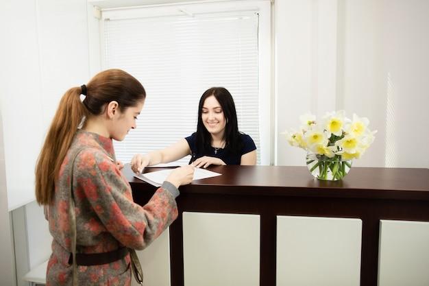 Administrator der jungen frau in einer zahnklinik an dem arbeitsplatz. aufnahme des kunden