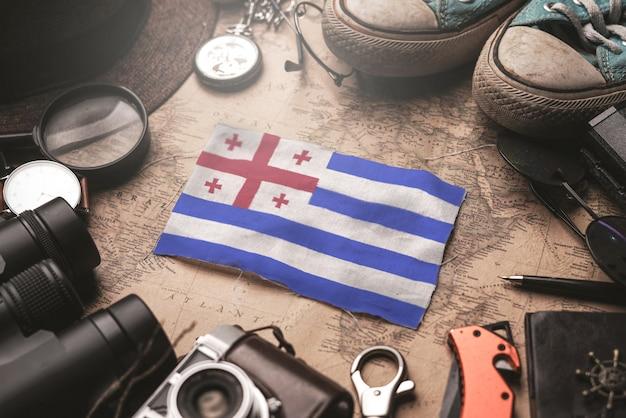 Adscharien-flagge zwischen dem zubehör des reisenden auf alter weinlese-karte. touristisches bestimmungsort-konzept.