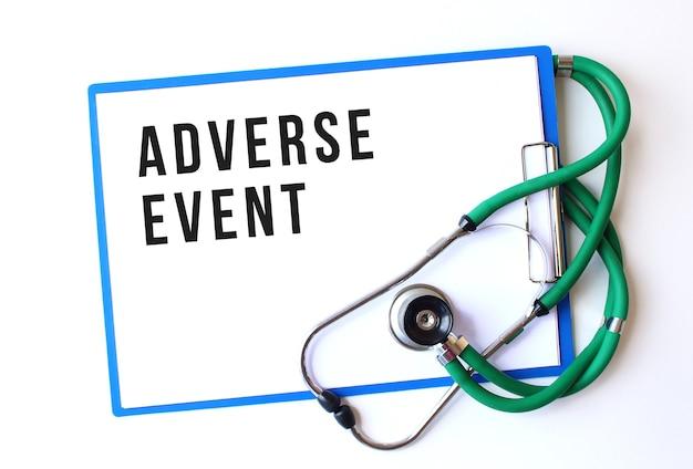 Adverse event-text auf medizinischem ordner mit dokumenten und stethoskop auf weißer oberfläche