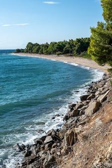 Ägäische felsige küste griechenlands, strand mit wachsenden bäumen und büschen