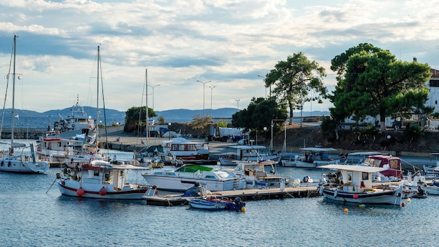 Ägäischer seehafen mit mehreren festgemachten yachten und booten, hölzerner pier, klares wetter in neos marmaras, griechenland