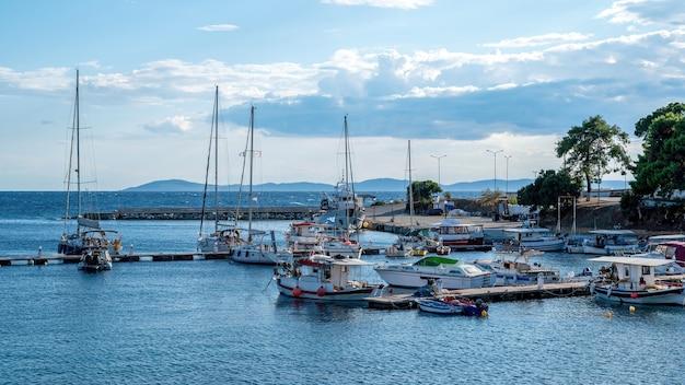 Ägäischer seehafen mit mehreren festgemachten yachten und booten, holzpfeilern, klarem wetter in neos marmaras, griechenland