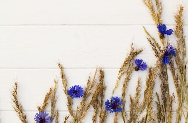 Ährchen und kornblumen auf einem weißen hölzernen hintergrund. flach liegen. speicherplatz kopieren.