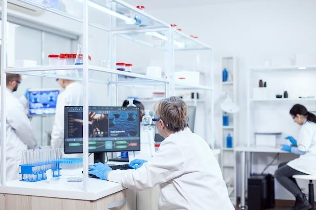 Älter gealterter medizinischer chemiker, der an einem leistungsstarken computer in einer modernen einrichtung arbeitet. leitender wissenschaftler im pharmazeutischen labor, der genetische forschung mit laborkittel mit team im hintergrund durchführt.