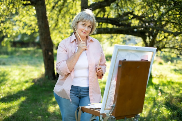 Ältere 60-jährige hübsche blonde kaukasische frau in freizeitkleidung, die ein bild auf leinwand malt, mit staffelei und pinsel posiert und im sommer draußen in einem schönen grünen sonnigen garten posiert.