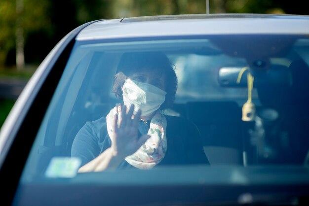 Ältere ältere frau, die eine gesichtsmaske trägt, während sie während der covid-19-epidemie im auto sitzt