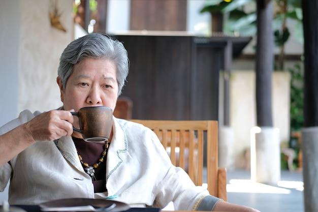 Ältere ältere frau, die kaffee-tee trinkt
