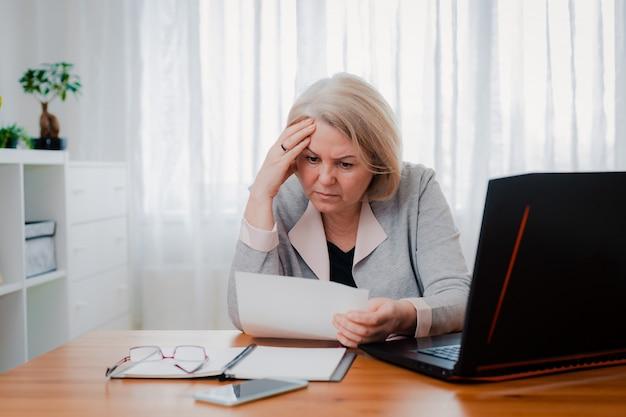 Ältere ältere frau kämpft am computer mit papierdokumenten, verwirrt von der geschäftsentscheidung