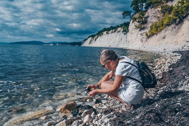 Ältere ältere reisende rucksacktourist reife frau touristin, die fotos an der küste macht
