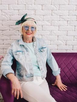 Ältere ältere stilvolle frau in blauer sonnenbrille und jeansjacke sitzen auf dem sofa im loft-interieur