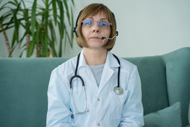 Ältere ärztin, die headset-videoanruf trägt, spricht mit webkamera, die virtuellen patienten online berät