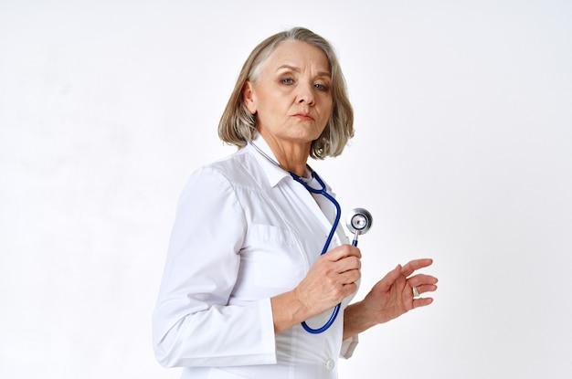 Ältere ärztin im weißen kittel medizinstethoskop