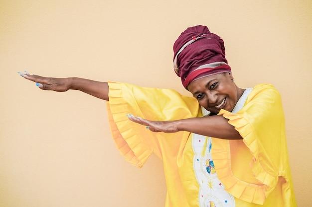 Ältere afrikanische frau, die draußen tanzt