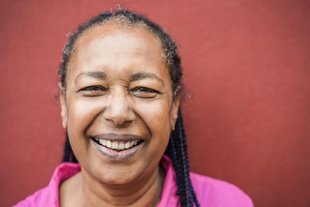 Ältere afrikanische frau, die vor der kamera im freien lächelt - fokus auf augen