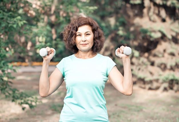 Ältere aktive frau mittleren alters, die übung in einem park im freien macht