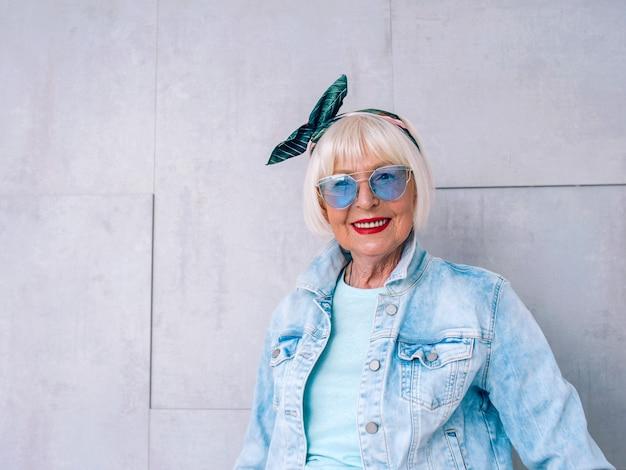 Ältere alte stilvolle frau mit grauem haar mit modischem stirnband und blauer brille