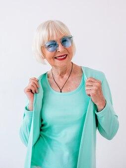 Ältere alte stilvolle fröhliche frau in blauer sonnenbrille und türkisfarbener kleidung