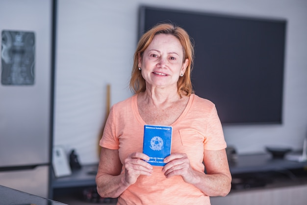 Ältere arbeitnehmerin, die in der hand die brasilianische arbeitskarte hält. ältere frau mit brasilianischer arbeitskarte