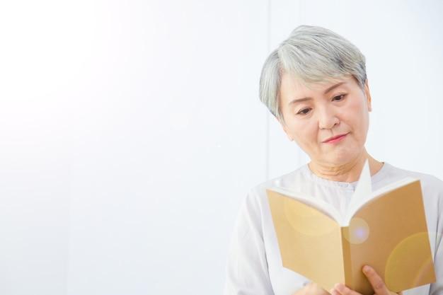 Ältere asia-frau liest buch auf weißem hintergrund.