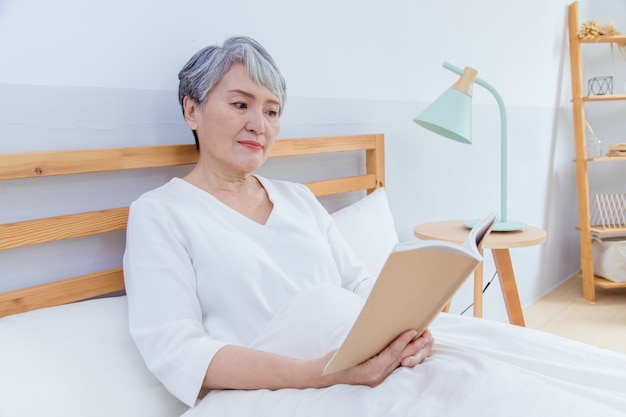 Ältere asia-frau sitzt auf dem bett und liest buch.