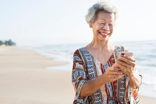 Ältere asiatin, die ein telefon am strand verwendet