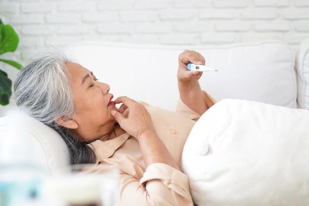 Ältere asiatin liegt krank auf dem sofa im haus nehmen sie medikamente gegen fieber ein, wie vom arzt verschrieben. und verwenden sie ein digitales thermometer, um die temperatur zu überprüfen. gönnen sie sich zu hause
