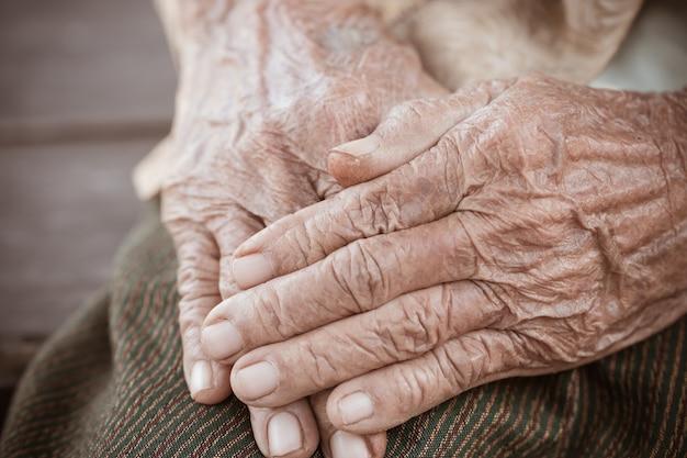 Ältere asiatische frau der hände ergreift ihre hand auf schosspaaren von älteren gerunzelten händen im gebet
