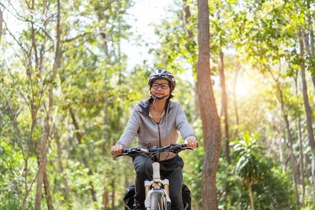 Ältere asiatische frau, die fahrräder im park reitet