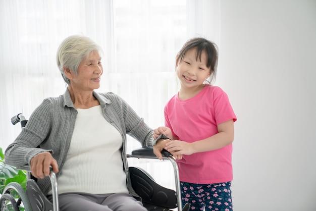 Ältere asiatische frau, die mit ihrem enkelkind auf einem rollstuhl sitzt