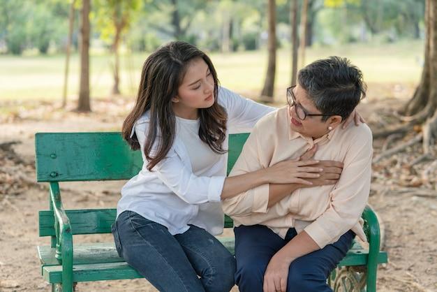 Ältere asiatische frau, die unter brustschmerzen mit ihrer tochterhilfe und -unterstützung leidet, während sie entspannt auf bänken im park sitzt