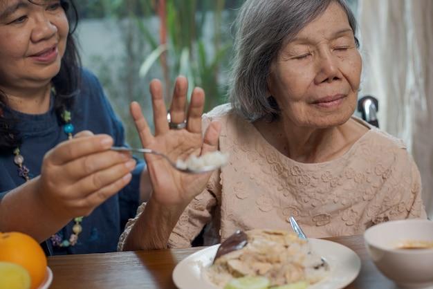 Ältere asiatische frau gelangweilt vom essen.