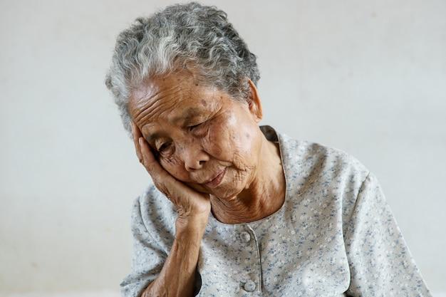 Ältere asiatische frau hatte kopfschmerzen