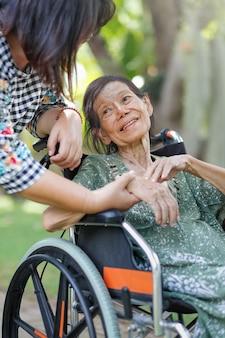Ältere asiatische frau im rollstuhl zu hause mit tochter passen auf