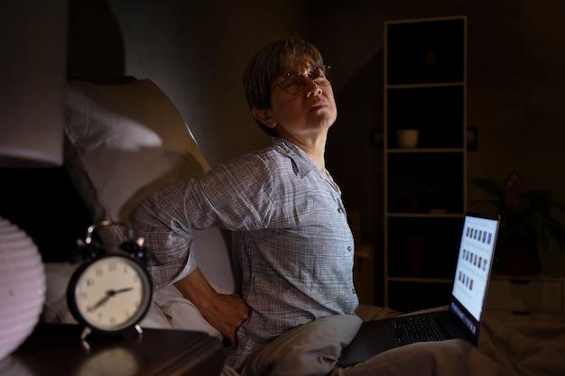 Ältere asiatische frau mit wunden und muskelschmerzen vom laptopgebrauch im bett