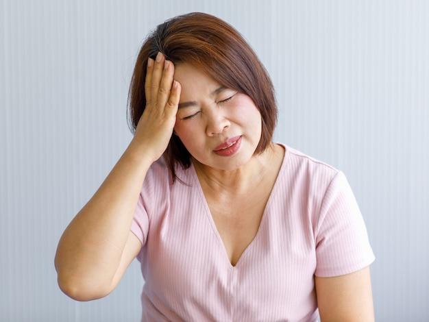 Ältere asiatische frau mittleren alters, die schmerzen durch plötzliche kopfschmerzen und schlaganfall verspürt und ihren kopf mit einem gestressten gesicht hält. konzept des gehirn- und kopfproblems.