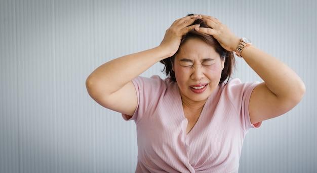 Ältere asiatische frau mittleren alters, die schmerzen durch plötzliche kopfschmerzen und schlaganfall verspürt und ihren kopf mit einem verzerrten und sich windenden gesicht hält. konzept des gehirn- und kopfproblems.