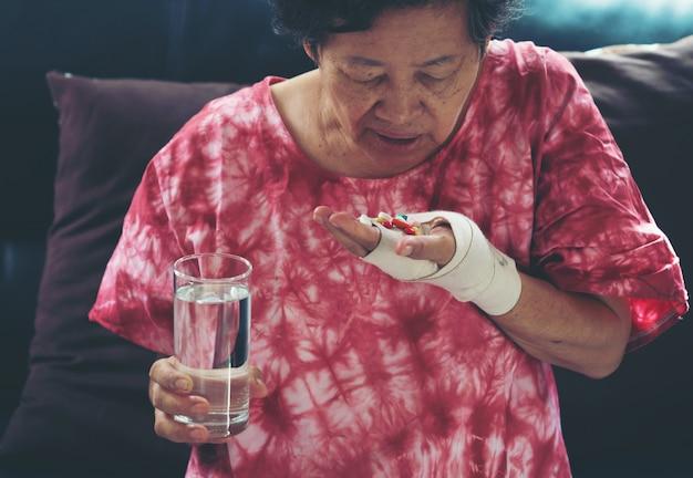 Ältere asiatische frau nehmen pillenmedizin an hand
