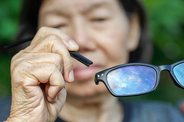 Ältere asiatische frau reparieren zerbrochene brille