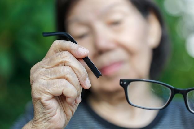 Ältere asiatische frau repariert kaputte brille