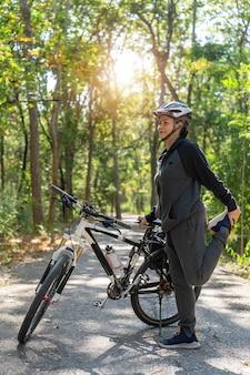 Ältere asiatische frau streckt muskeln mit fahrrädern im park