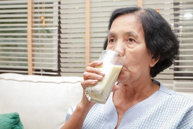 Ältere asiatische frauen trinken kalziumhaltige milch, um osteoporose vorzubeugen.