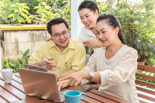 Ältere asiatische freunde, die laptops und tablets im pflegeheim verwenden.