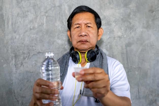 Ältere asiatische mannsorge in der sportkleidung, die medizin hält.
