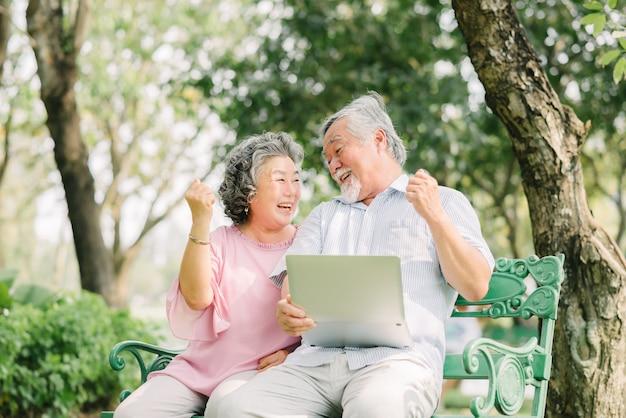 Ältere asiatische paare, die mit laptop im park lachen