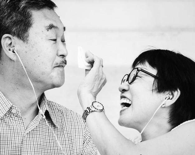 Ältere asiatische paare, die zusammen musik hören