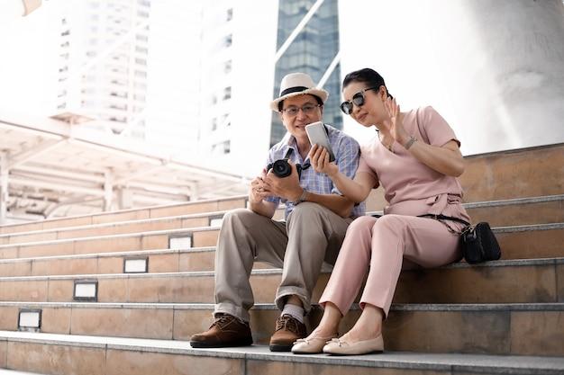 Ältere asiatische paare sitzen auf reisen auf der treppe und haben spaß beim videoanrufen.