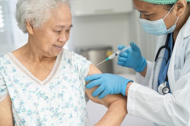 Ältere asiatische seniorin mit gesichtsmaske, die covid19- oder coronavirus-impfstoff erhält