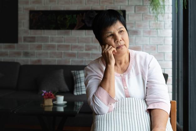 Ältere asien-frau, die seitlich denkt und schaut, denkt und sich wundert
