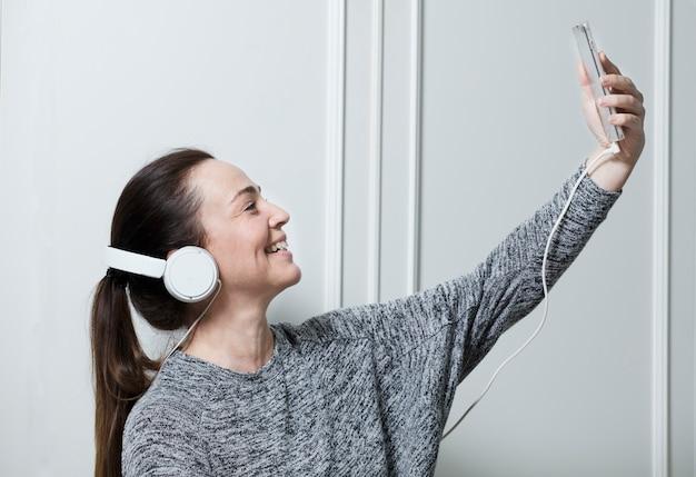 Ältere attraktive frau, die videokonferenz von zu hause aus macht